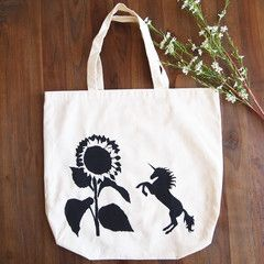 A Unicorn attacks a very large, but unsuspecting sunflower. Hand painted tote bag by Grafeeq