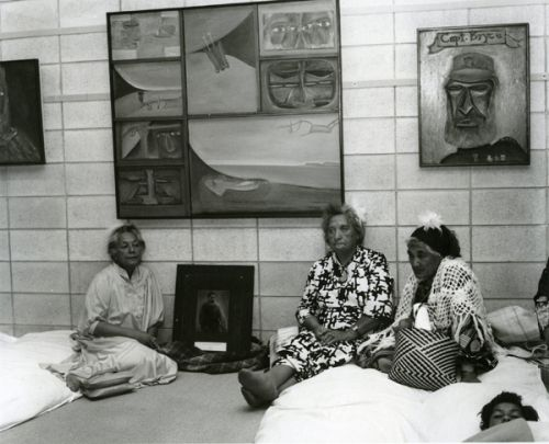 "Ans Westra Netta Wharehoka, Ngahina Okeroa and Materena Ran - Kupa from Taranaki sit with a photograh of Te Whiti at Selwyn Muru's exhibition opening - ""Parihaka"", The Dowse Art Museum, Lower Hutt, 1979 Silver gelatin print 212 x 255mm"