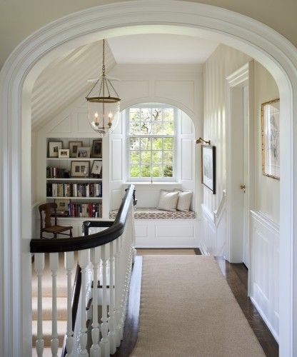 like everything about this staircase landing: arches, window seat, book shelf, dark/white wood and light fixture