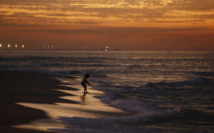 Seorang gadis Palestina bermain di pantai Kota Gaza setelah matahari terbenam.