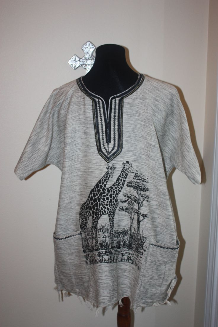 This men's short sleeve shirt has a neckline and pockets embellished with black stitching. It features a black giraffe motif, and has hand-tied fringe at the hem. Shirt is 25 inches across and 29 inches long. Hand crafted by the Lulu mamas in Uganda.  These men's shirts are so unique! Each shirt is sewn by a Lulu mama or daughter trained in tailoring through the Lulu program. They are made from beautiful African cloth, and each shirt has special details that blend traditional African design…