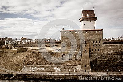 Embankment in the city of Narva in the spring with bare trees, beautiful clouds and with houses, architecture, towers, churches in the background. In the turbulent river there are reflections of trees.