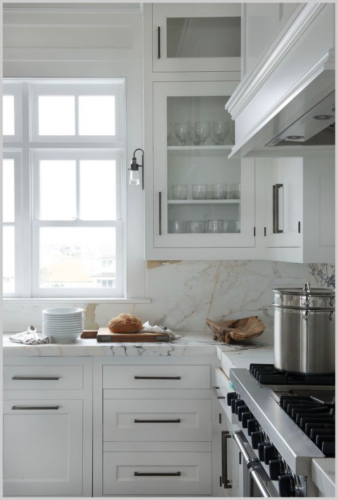 A white wood panel hood is mounted to a gray and white marble slab backsplash above a stainless steel oven range. White shaker cabinets donning oil rubbed bronze pulls and a marble countertop are positioned beneath white upper cabinets. SSS Design Interiors Photo by JaneBeiles