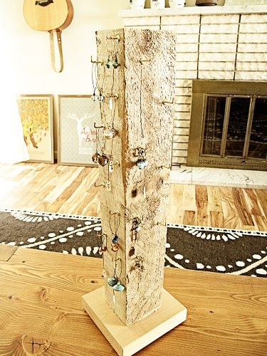 Reclaimed wood 4″x4″ post nailed and glued to a pine base with eye hooks screwed into it for hanging earrings.