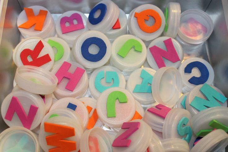 Lletres per crear paraules. Fetes amb goma eva i aferrades damunt taps de plàstic.