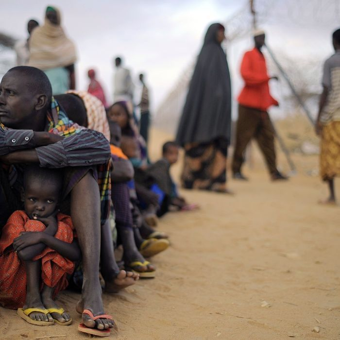 A Somali father shelters his daughter in a queue in the Dadaab refugee complex in Kenya.