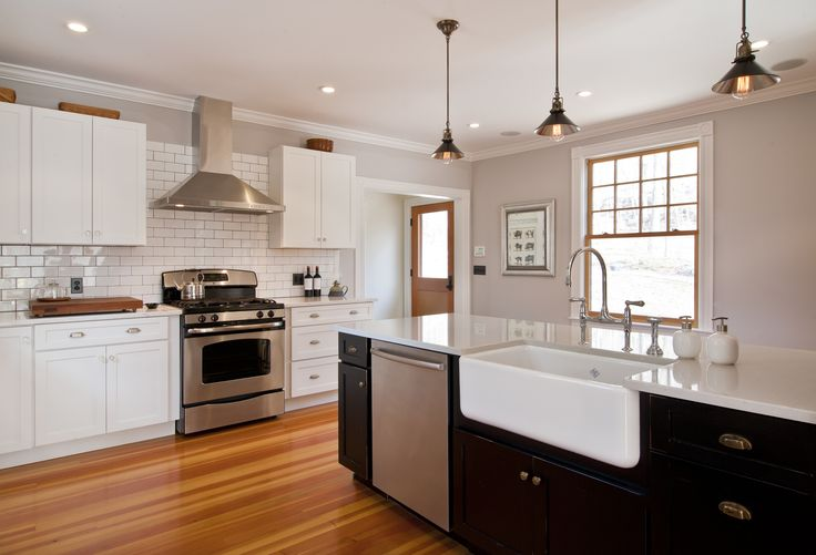 modern farmhouse kitchen: black and white shaker cabinets under white quartz counters, white subway tiles with black grout, new natural wood Marvin twelve-over-one windows are all a bit unexpected