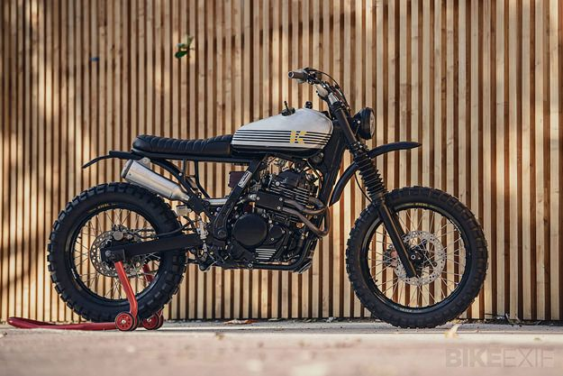 'Dos' is a short, sharp shock based on a 1991 NX650. It's styled even more aggressively than the first Kiddo Motors build, and it's fast: Sergio has completely rebuilt the motor, adding a Keihin FCR carb from a Honda CRF450R. A custom 2-into-1 exhaust feeds into a SuperTrapp muffler. #CustomMotorcycle #HondaCRF450R