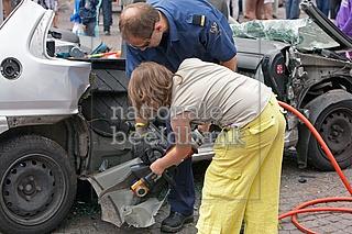 meisje helpt een brandweerman met het openknippen van een auto