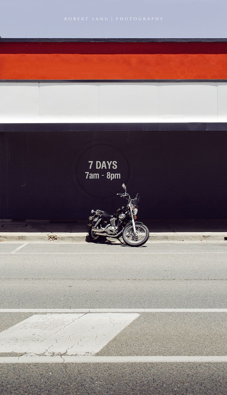 https://flic.kr/p/Rh48Cr | Parked motorcycle out the front of a shop | A black motorcycle parked on an empty street out the front of a shop