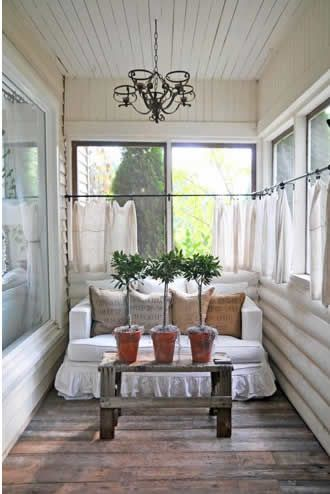 Beautiful enclosed porch idea for a narrow space. The loveseat gives the illusion of a wider space. The café curtains are awesome for privacy without blocking the light. The bench and wood floors are a great element to keeping it natural.