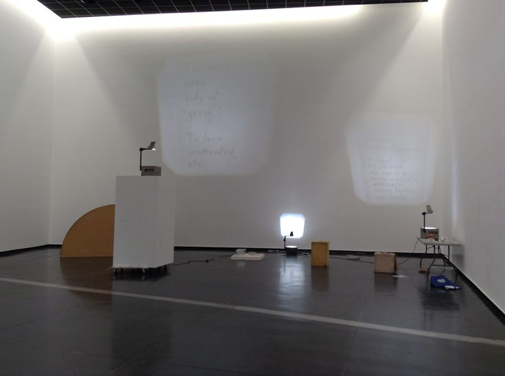 This is... (information) (2015) by Alex Vivian, overhead projectors, stained cushion, comic book pieces, hair, magazine, foam, pasta meal, shoe box, dirty plinth, cream cheese, Tupperware, found object, permanent marker, masking tape, acetate dimensions variable