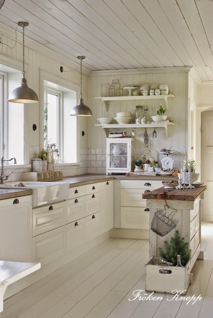 White kitchen in the old style, painted wooden floor, small rustic island, stamp