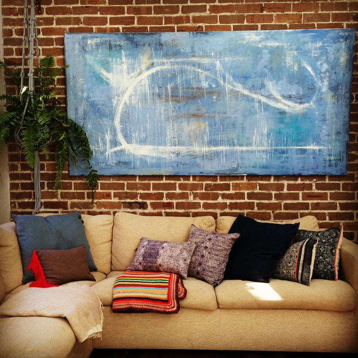 """Living room warmth, colour, light and textures.  """" blue whale"""" oil on canvas, Keren Rockman printed cushions, nana's crochet throw, original wall exposed brick in all its imperfection. hanging plant macrame."""