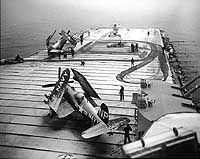 """USS Valley Forge (CV-45)  Crewmen use flight deck tractors with power brooms to sweep snow from the carrier's flight deck, during operations off Korea, circa early 1951. Photo is dated 8 May 1951, but Valley Forge ended her second Korean War deployment in late March of that year. Plane parked in the foreground is a F4U-4 """"Corsair"""" fighter. Those on the forward flight deck are an AD """"Skyraider"""" attack plane and a HO3S helicopter."""