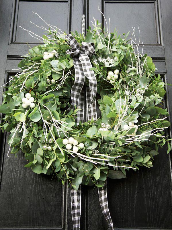 Kranz aus gemischtem Grün wie Mistelzweig und Eukalyptus mit feinen weißen Zweigen und schöner weiß-grüner Schleife.
