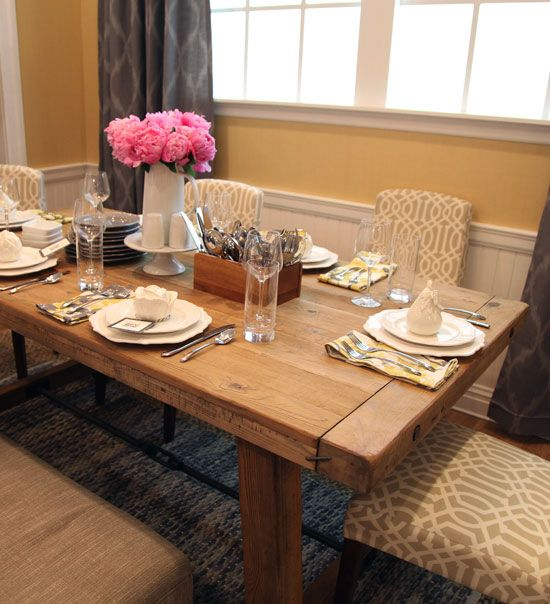 They hung three lampshades over the table as pendants, used really fun patterned chairs and paired them with a rustic wood dining table.  The table was topped with pretty white dishes, yellow linens and a playful cutlery caddy.