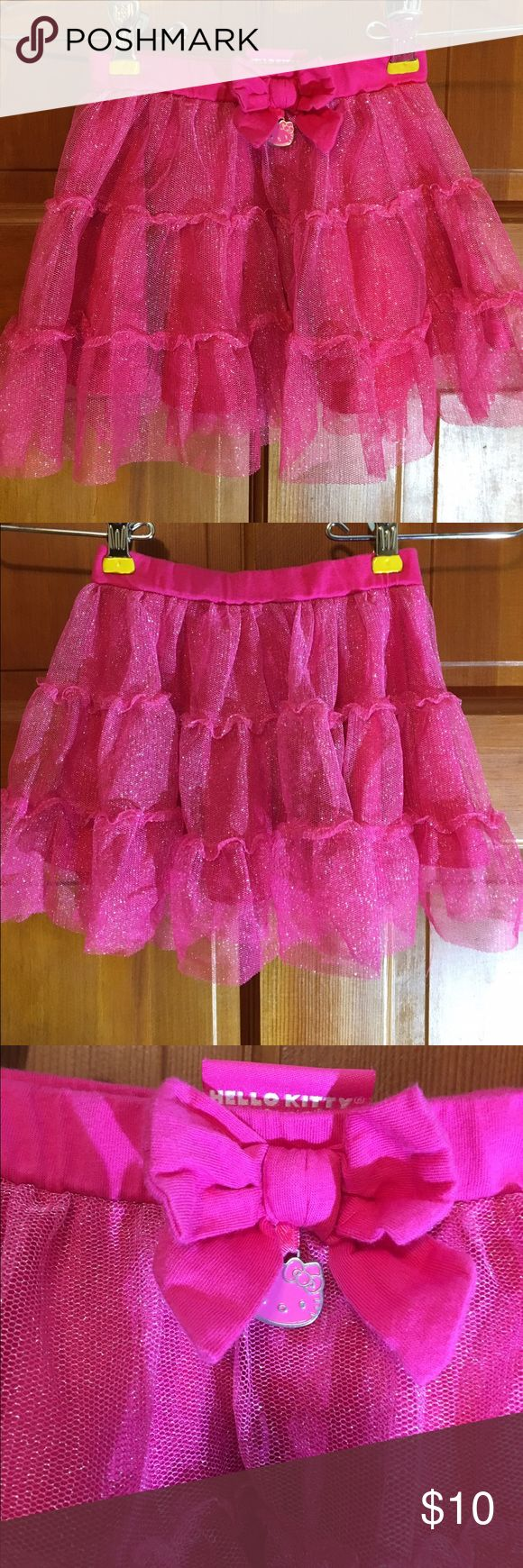 Hello Kitty Pink tutu skirt size 24 Months Hello Kitty tutu skirt.  Pink chiffon outer with solid pink polyester lining. Cotton waistband embellished with a bow and Hello Kitty charm. Cute with leggings under but long enough to wear alone. Size 24 months. Wash inside out, cold, gentle cycle. Tumble dry low. EUC. Hello Kitty Bottoms Skirts