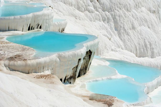 Pamukkale Small Group Tour from Kusadasi Discover Pamukkale with the small group tours of locals. The tour itinerary is Hierapolis Ancient City, Travertine Terraces of Pamukkale. Also, delicious Turkish lunch is included.You will meet your guide at your hotel in Kusadasi and you will drive to Pamukkale. You will see the Necropolis (cemetery) of Hierapolis which is one of the biggest ancient cemeteries in Anatolia with 1.200 graves, Roman Bath, Domitian Gate, and the Main Stree...