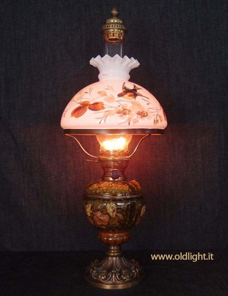 """Bellissima lampada  in maiolica, base in metallo dorato, origine tedesca primi 900, assolutamente autentica; Bruciatore MATADOR 20 ''' ( upper gallery );  Tubo vetro soffiato Matador 20'"""" con raro para-fiamma in ottone; Paralume campana  in opalina (autentica) con decorazione  realizzata a mano."""