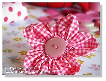 "5 Petal fabric flower w/button. Use 5- 3x3"" sqs. Fold into triangles - baste open edges - add next triangle - add button to finish."
