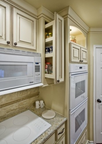 A wall cabinet pull-out spice pantry can be the ideal thing for a narrow space at eye level next to the cooktop.