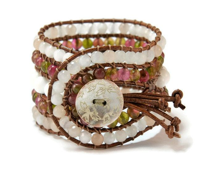 A 5 strands women's bracelet is handcrafted with semi precious stones of aventurine white onyx & crystals of high quality. All of them are framed by natural brown leather woven together with maroon cotton cord. This easy - to - wear design also features a metal, lightly bronze, vintage, flower closure. This gorgeous bracelet pairs beautifully with other gold tone pieces, but can also make a subtle shimmering statement worn alone.