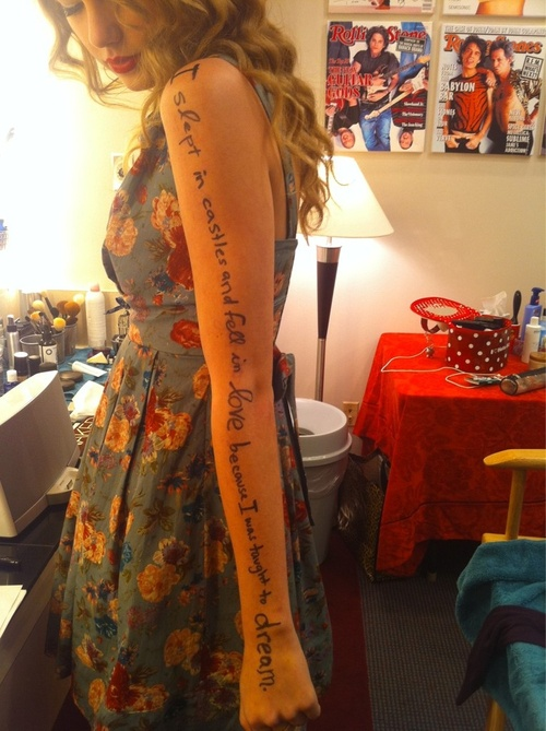 taylor swift writing on her arm for no reason, I'm sure she can afford paper