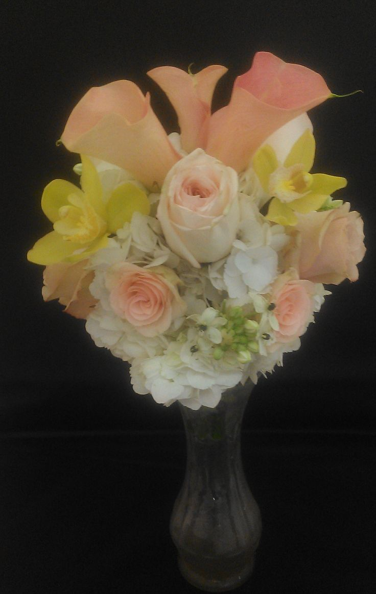 Highlighting peaches and pinks, this bridesmaid's bouquet features white hydrangeas, three different shades and sizes of roses, peach calla lilies, star of Bethlehem, and for a pop of color, yellow cymbidium orchids.  See more wedding bouquets, centerpieces, and more at www.jeffmartinsweddings.com