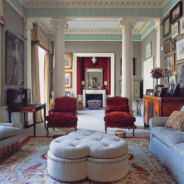 Английская гостиная: большие диваны икресла, мебель изтемного дерева, ковер, камин и картины.