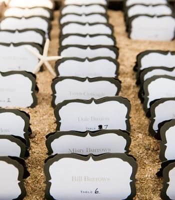 place cards displayed in a box with sand and starfish