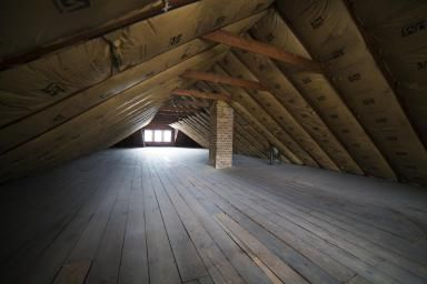 Empty Attic with Insulation on Roof - Cavan Images/The Image Bank/Getty Images