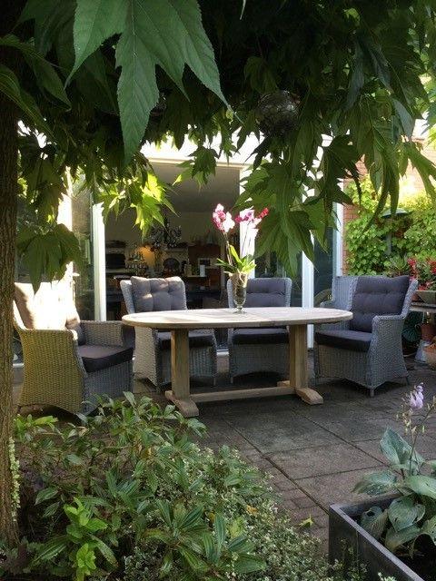 Ovalen tafel met royale stoelen voor in de tuin