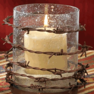 Barbed wire wrapped around a pillar candle holder.