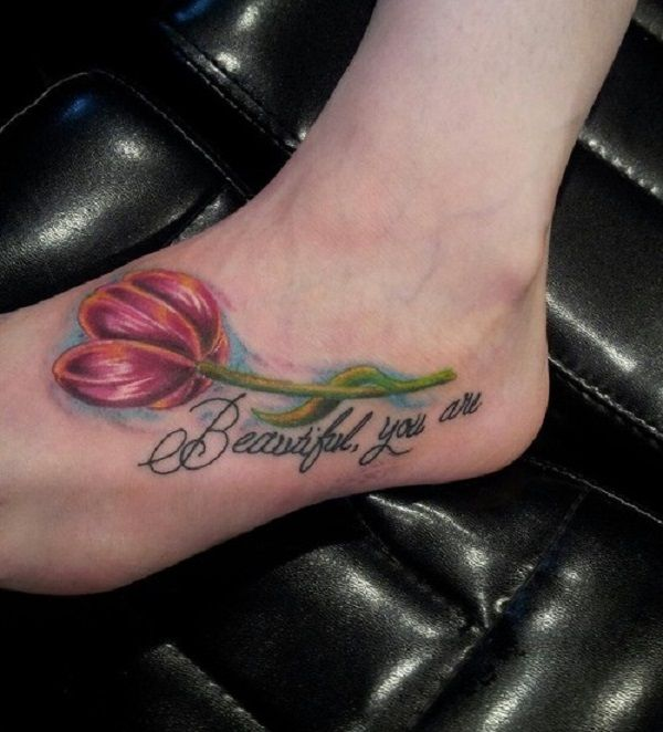 Red tulip tattoo on the foot. Cute and artistic at the same time. The addition of the quote only makes the tattoo design stand out even more.