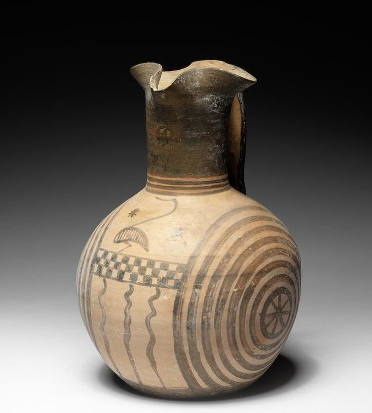 Attic terracotta oinochoe, Concentric Circle Group, Geometric Period, circa 8th century B.C. The globular body decorated in umber on the shoulder with a stylised bird standing on a chequered band, flanked on both sides by concentric circles, centred by a cross motif on one side and a central star design on the other side, another bird beneath the handle, 22 cm high. Private collection
