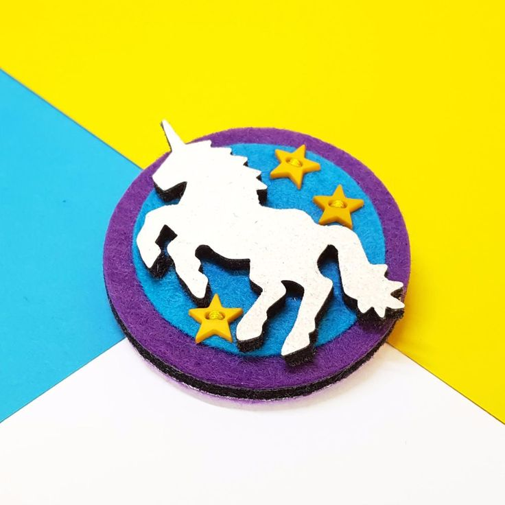 This sparkly handmade brooch would make an awesome gift for unicorn lovers - or for anyone who needs a bit of encouragement to Fly High and Reach for the Stars! Full Description: Fly High Unicorn Brooch made from 100% wool felt Decorated with wool blend felt (30% wool, 70% viscose) glitter fabric and tiny yellow star buttons Measures approximately 5cm x 5cm Fastens with a 3cm brooch pin with safety catch Metal Pin Badge measures approximately 2.5cm COLOUR: Purple, T...