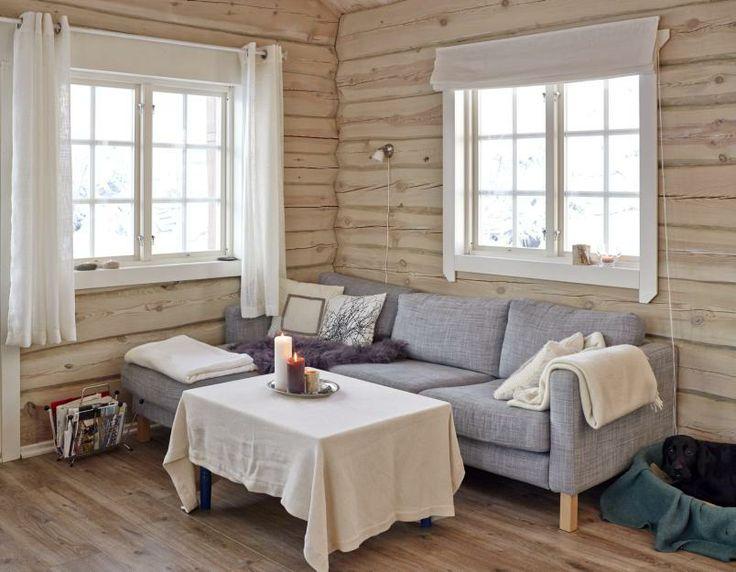 Tømmerhytte i Hedalen i tradisjonell stil. Stue innredet i gråtoner. Sofa fra Ikea.