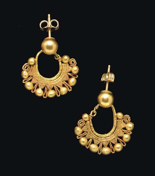 A PAIR OF NABATEAN OR EASTERN ROMAN GOLD EARRINGS   CIRCA 1ST-2ND CENTURY A.D.   Each formed from a plain tapering hoop, adorned with clusters of granules, the underside joined to plain wires framing a beaded wire, with a fringe of seven triangles of granulation, each capped with a large hollow sphere, and interspersed by twisted wire loops, each end terminating in a voluted twisted wire beside a small hollow sphere; joined to modern gold balls and ear posts