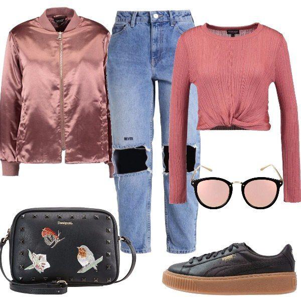 Jeans largo strappato sulle ginocchia, maglia con scollo tondo rosa scuro, giubotto bomber rosa lucido con colletto alla coreana, sneakers basse nere, occhiali da sole specchiati rosa e borsa a tracolla con patch.