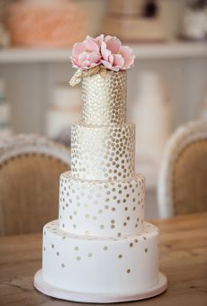 """This wedding cake with gold polka dot accents gives us a Kate Spade vibe. Top it with big pink flowers a few gold leaves for an extra """"pow."""""""