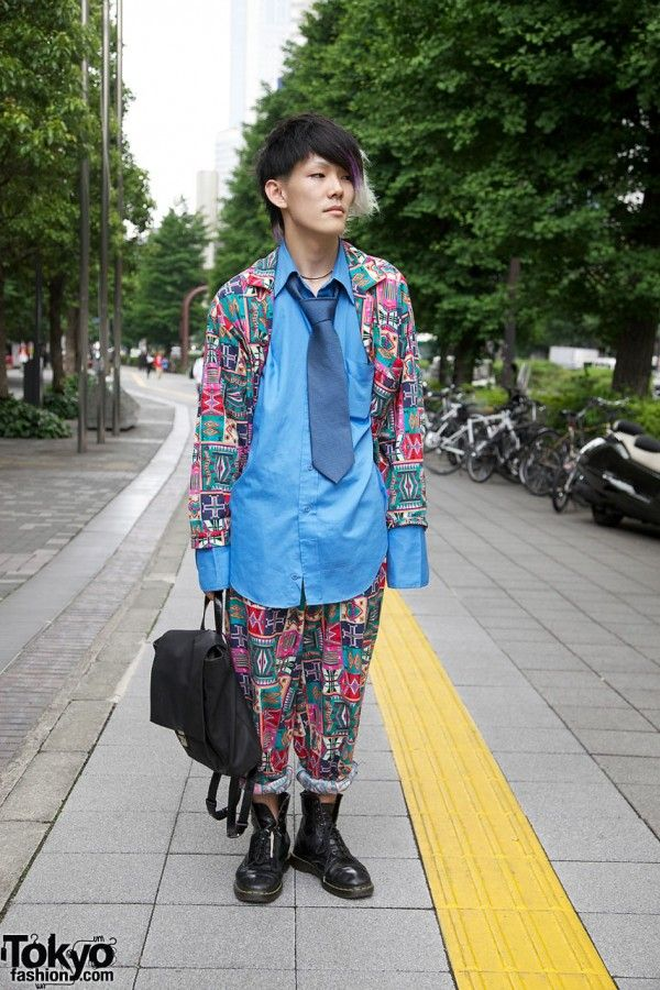 Meet Ryo, a colorfully-dressed 18-year-old Japanese student that we ran into on the street in Shinjuku. Beyond his clothing, Ryo's purple-green-gray-white-black long-bangs hairstyle made an impression when we first spotted him. Ryo is wearing an outfit put together with multiple items from the hip Harajuku resale/vintage shop Daybreak that features matching rolled-up pants and a jacket in a colorful patchwork pattern, a blue shirt with extra-long sleeves, and a loosely tied tie. Ryo is also…