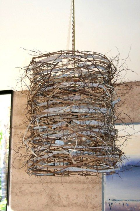 skinny twigs wrapped around a wire frame light shade
