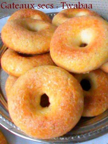 Gateaux secs Twabaa à clocher : Battre 3 oeufs et 1 verre de sucre, ajouter 1 verre d'huile. Rajouter un zeste de citron, un peu de vanille, 1 sachet de levure. Incorporer doucement de la farine pour former une pâte très molle. Laisser reposer 10 min. Huiler ses mains, former une petite boule de pâte, puis avec le bras d'une cuillère en bois, enfoncer au milieu et tourner rapidement pour former le trou. Badigeonner la surface de beurre et saupoudrer de sucre. Enfourner Th. 4-5 pour dorer.