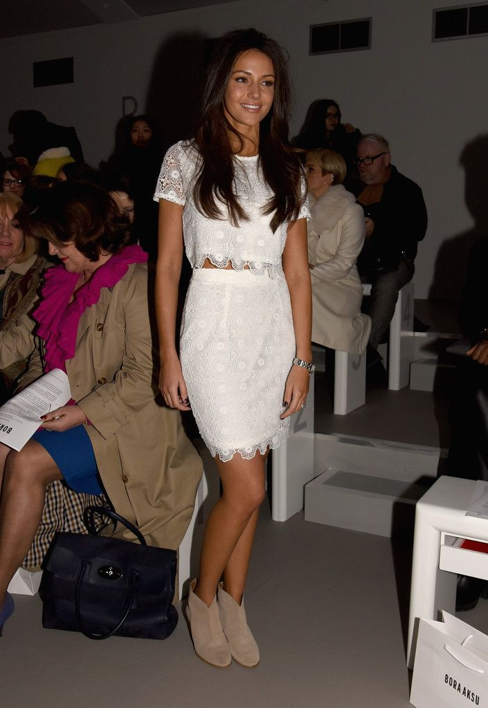 """20 Feb 2015 – Michelle Keegan attends the Bora Aksu show during London Fashion Week Fall/Winter 2015/16 at Somerset House in London, England — Crop Top: Michelle was trendy & girly in a white lace crop-top from her """"Lipsy"""" line • Mini Skirt: A matching """"Lipsy"""" mini skirt completed the cute outfit • Ankle Boots: For a touch of edge, Michelle donned a pair of nude suede ankle boots."""