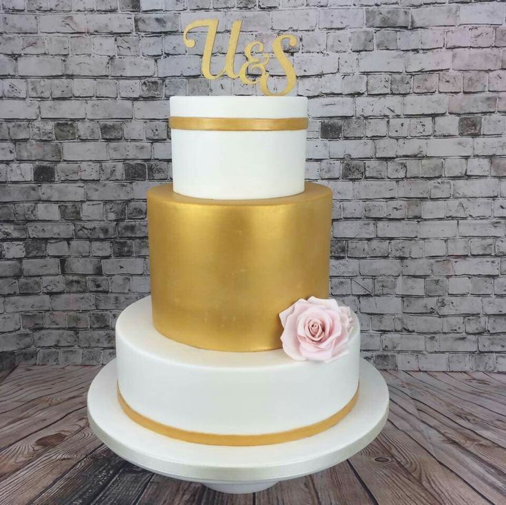Elegant, simple, gold and white fondant double barrel tiered wedding cake with handmade custom monogram topper and pink sugar paste pink roses
