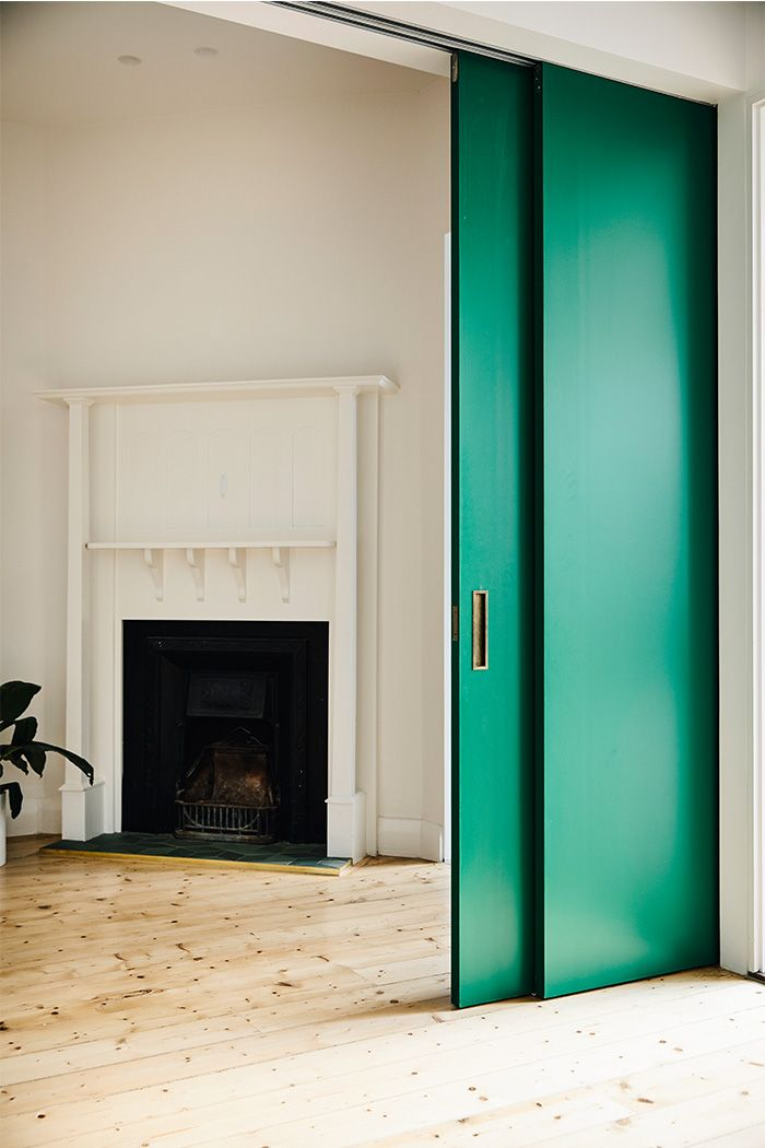 Wolveridge Architects Art Deco Mid Century Modern Light Filled Open Plan Heritage Renovation Cottage in Melbourne, Australia featuring Timber Flooring and Open Indoor Wood Burning Fire with Green Feature Door