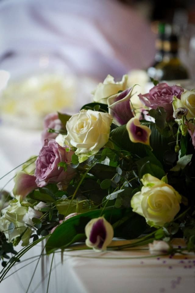 Close up image of top table arrangement, Vermeer Calla Lilies and Avalanche and Memory Lane Roses