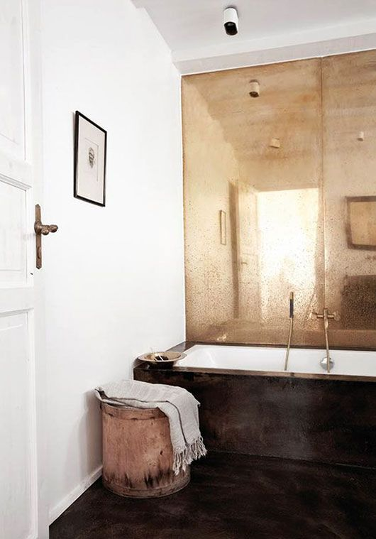 Loving the aged effect mirror and contrasting dark earthy tones of the flooring in this bathroom