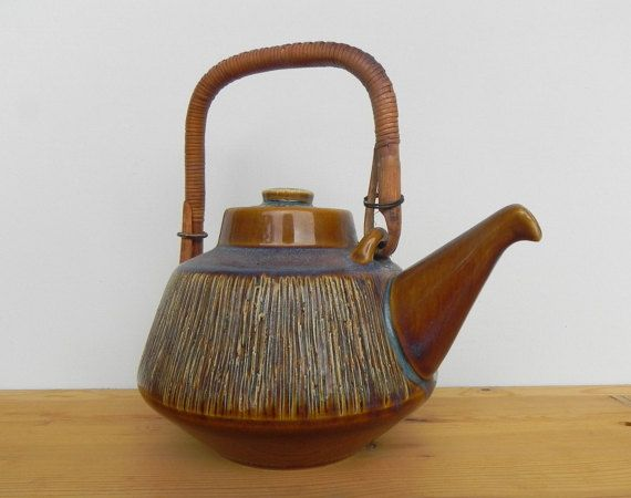 SØHOLM Denmark Stoneware Svend Aage Jensen teapot with a raffia wrapped handle from the 1960s.  This wonderful piece of Mid Century Danish pottery is decorated with sgraffito technique before burning which gives it a lovely rough surface. My mother has always taught me, that the most wonderful thing about pottery is not what you can see, but what you can feel: Try closing your eyes, she would say and let your fingers wander all across the surface. A good feeling in your fingers is what…
